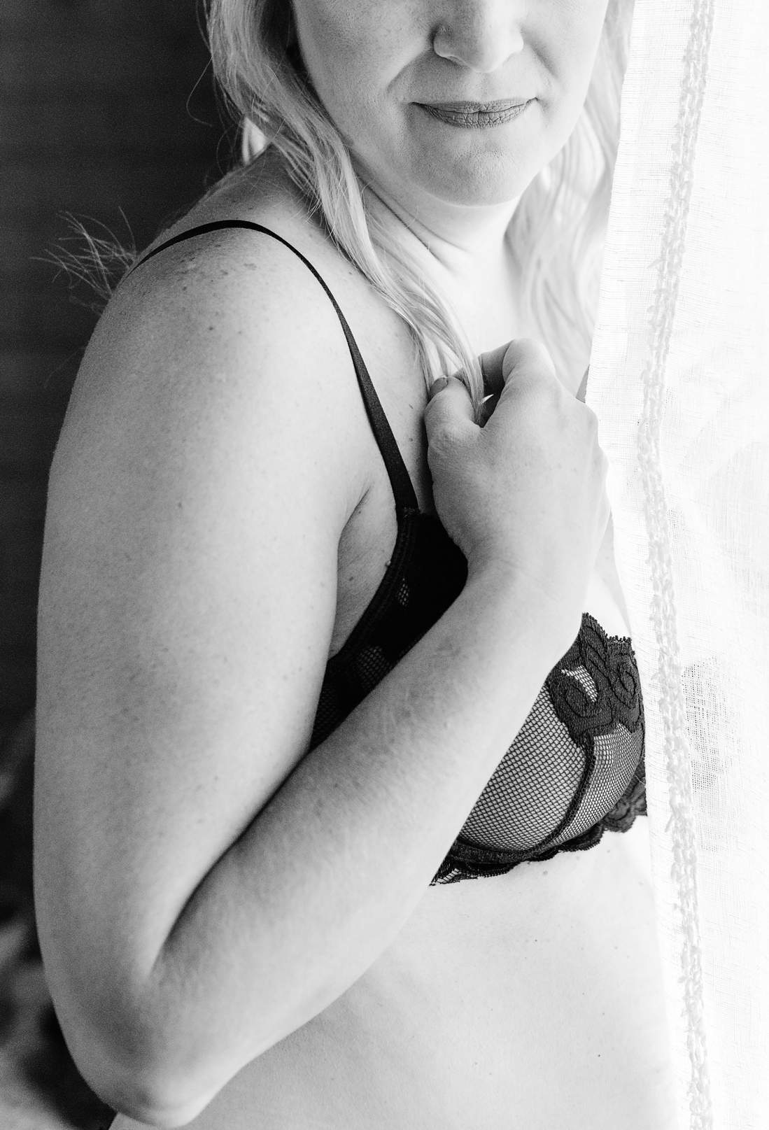 black and white boudoir photo by self love photo co woman in lingerie peeking out from curtain